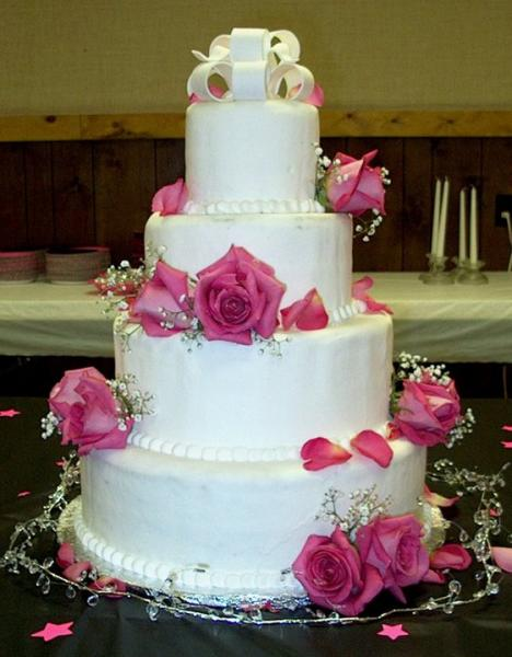 White wedding cake decorated with fresh pink roses