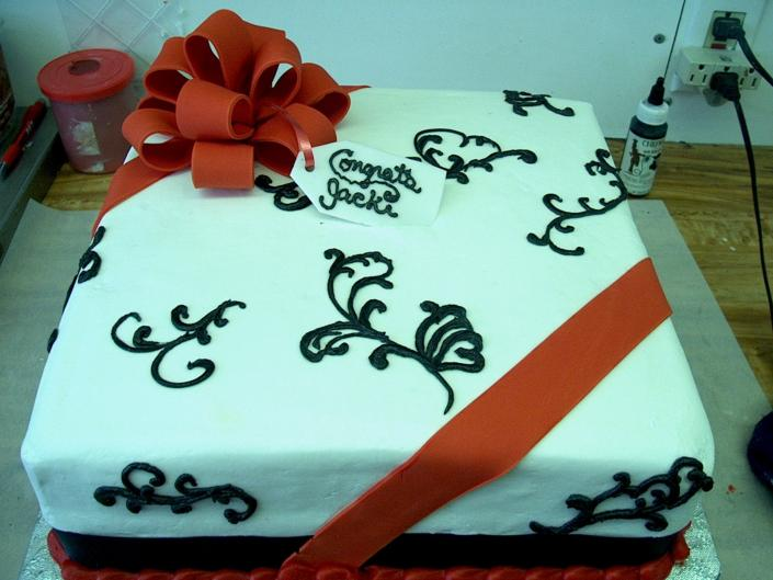 [Image: Very unique sheet cake decorated with red ribbon]