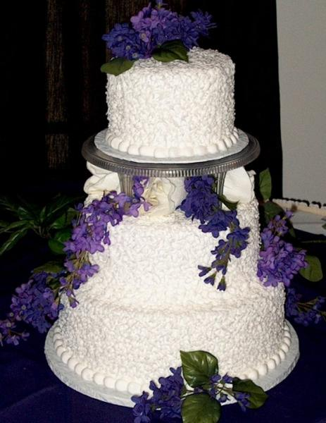 [Image: White wedding cake trimmed in purple]